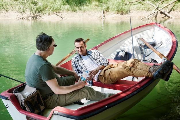 Vissers zitten en ontspannen in boot