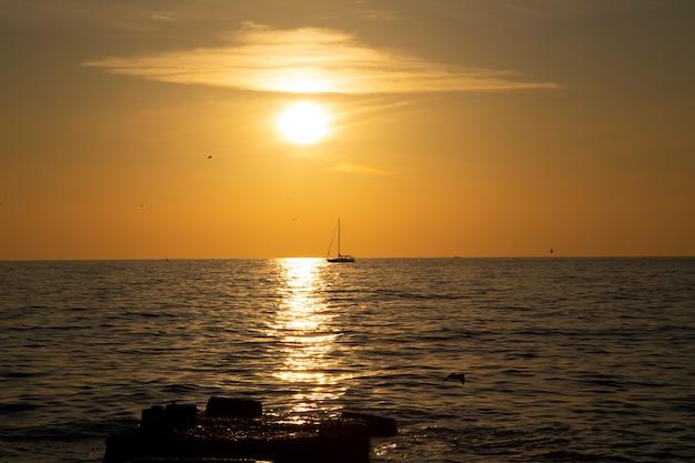 Vissersboot aan de horizon, zonsondergang aan zee. kalme zee, koraalhemel, avondvissen