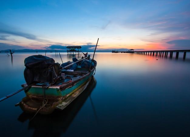 Vissersboot in de zee bij zonsondergang