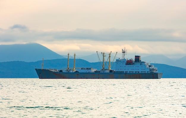 Vissersboot in grijze ochtend op de stille oceaan voor de kust van het schiereiland kamtsjatka