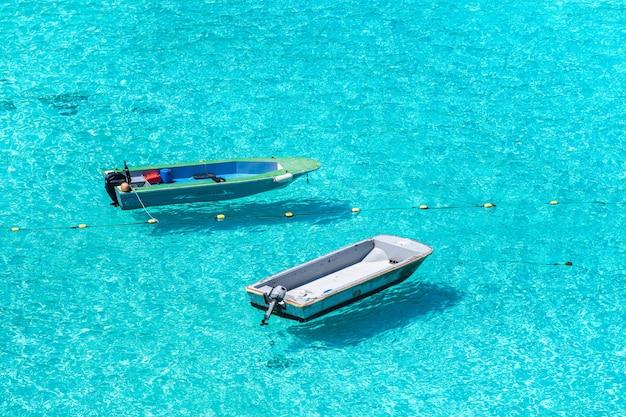 Vissersboten die op een zonnige dag boven de zee drijven.