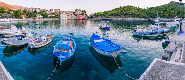 Vissersboten voor anker in de zee baai van assos dorp in een prachtige azuurblauwe inham in kefalonia, griekenland