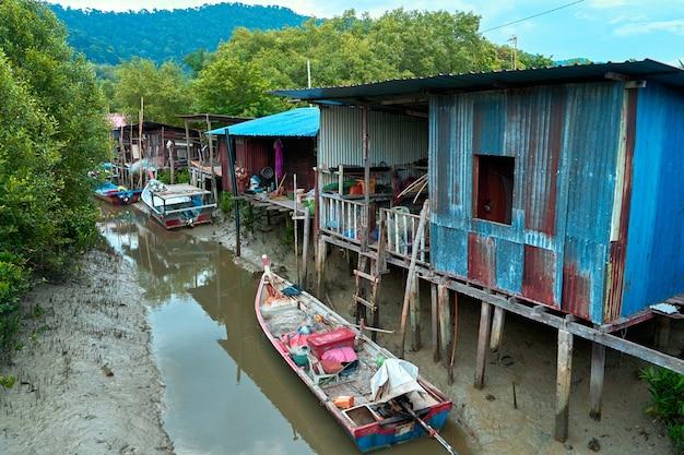 Vissersdorp in azië. boten bij vervallen huizen op palen