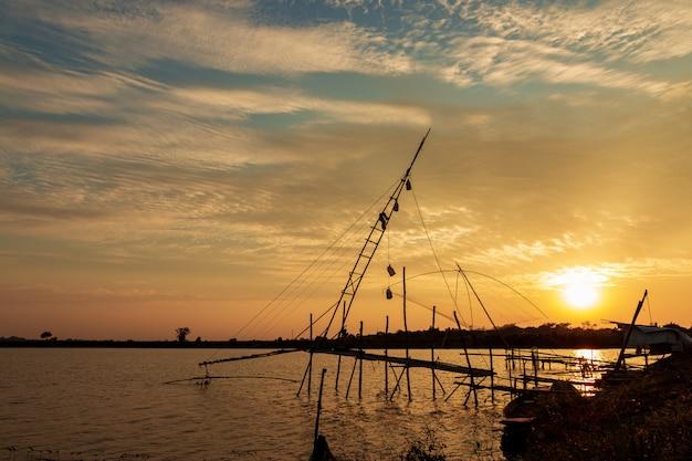 Vissershulpmiddelen in het meer bij zonsonderganghemel.
