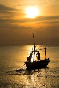 Vissersilhouet in zee bij zonsopgang