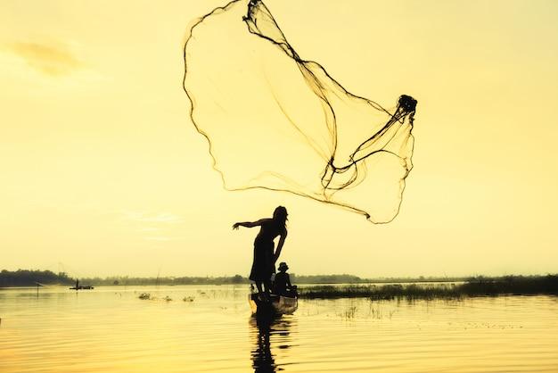 Vissersmens die onderdompeling het netto vissen bij meer met berg en blauwe hemelachtergrond werpen