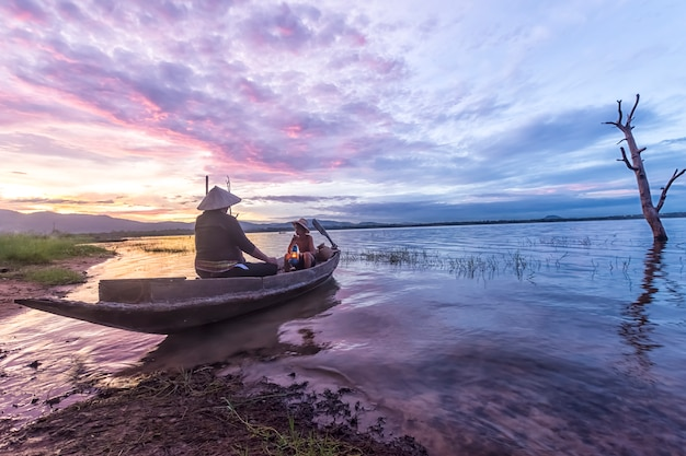 Vissersvader en kleinzoon die op de boot vissen