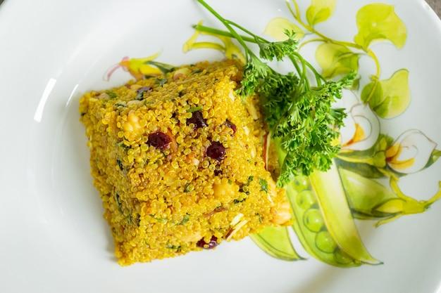 Vista superior quinoa y ensalada en un plato blanco con flores amarilla concepto comida saludable