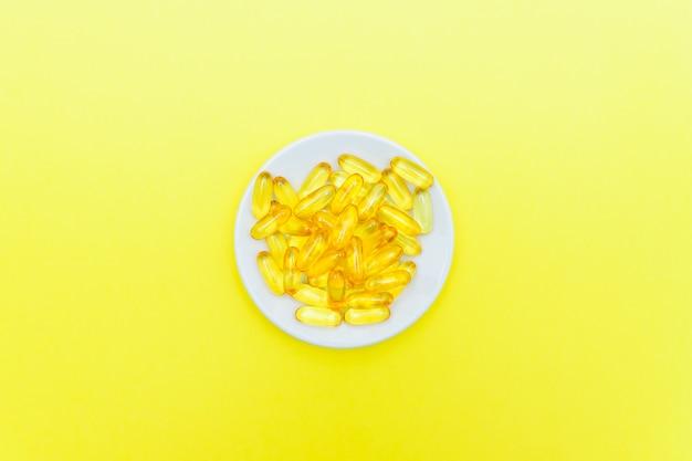 Vistraancapsules in een witte plaat op gele muur. bovenaanzicht, plat lag, kopieer ruimte.