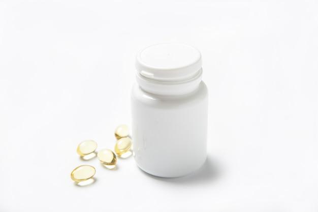 Vistraanpillen in een kruik op een wit. omega 3. vitaminen