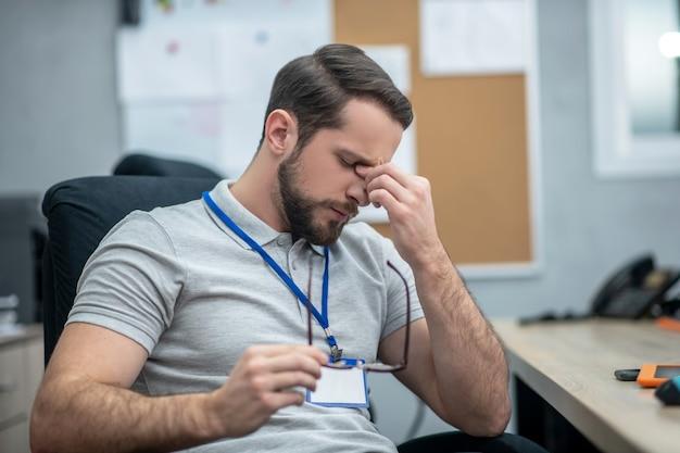 Visuele stress. moe jonge volwassen man met badge met gesloten ogen en glazen in de hand zittend in een stoel op de werkplek