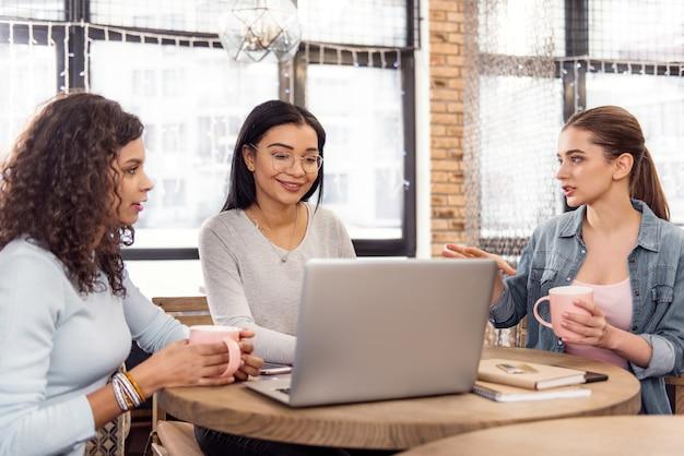 Vitale veranderingen. enthousiaste mooie drie studenten die presentaties bespreken onder het genot van thee en poseren in het café