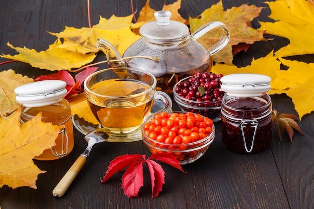 Vitamine-achtige duindoornthee in kleine glazen theepot met verse rauwe duindoornbessen en honing, volksmedicijn