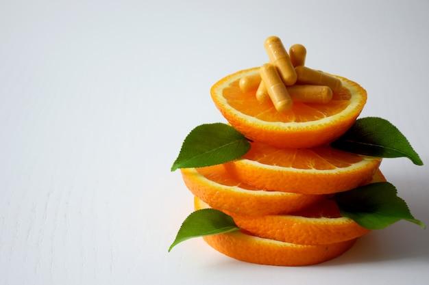 Vitamine c-capsules bovenop stukjes sinaasappel met kopie ruimte.
