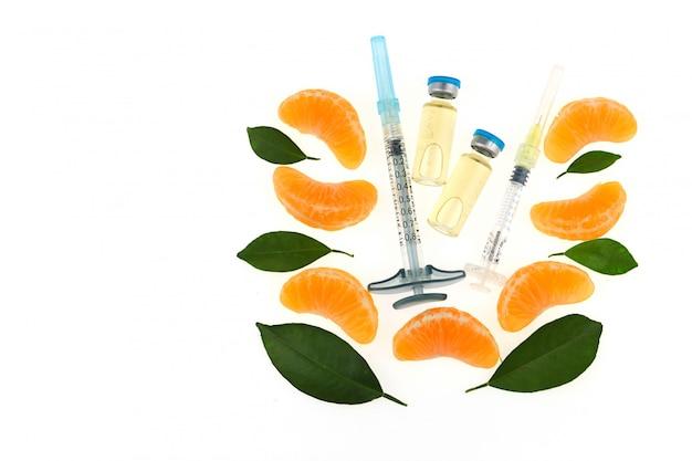 Vitamine c in ampullen, twee spuiten, sinaasappel. organische cosmetica concept