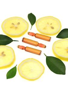 Vitamine c. serum met vitamine c, ampul, schijfjes citroen en citroenbladeren.