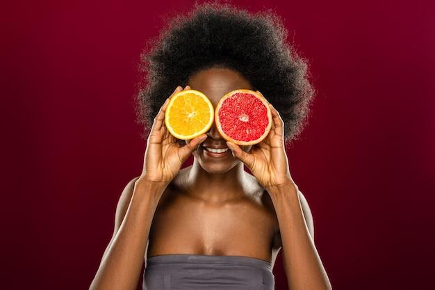 Vitamine c. vrolijke aardige vrouw die twee fruithelften vasthoudt terwijl ze tegen een rode muur staat
