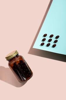 Vitamine capsules lecithine pillen en pil glazen fles op roze en blauwe achtergrond met trendy
