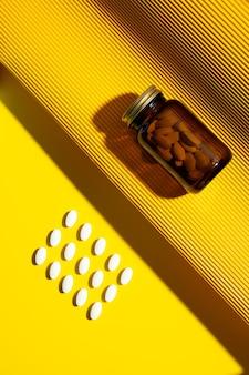 Vitamine capsules vitamine c pillen en pil glazen fles op gele achtergrond met trendy schaduwen