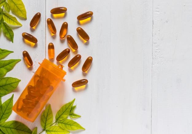 Vitamine d van visoliecapsules in een oranje fles op witte houten achtergrond
