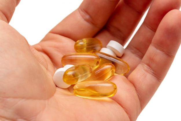 Vitamine e omega-3 visolie gele pillen in een hand vitaminen sportvoeding gezond