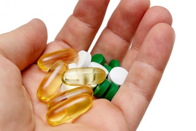 Vitamine e omega 3 visolie gele witte pillen in een dicht omhoog geïsoleerde hand
