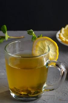 Vitamine gemberdrank met honing, munt en citroen in een glazen beker op een betonnen achtergrond verticale foto