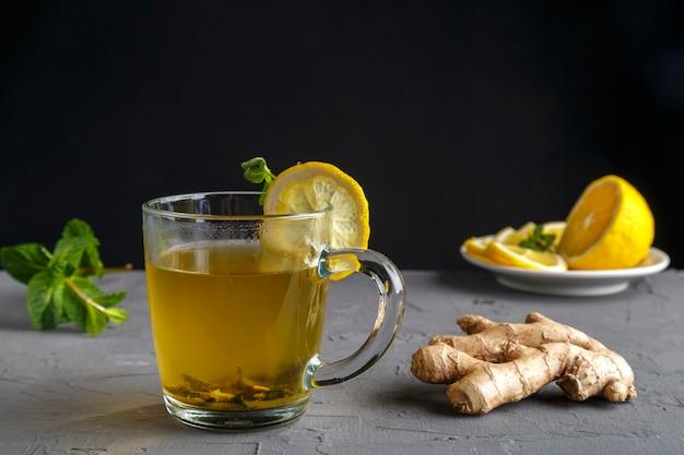 Vitamine gemberdrank met honingmunt en citroen in een glazen beker in de buurt van gemberwortel en citroen op een betonnen achtergrond. horizontale foto