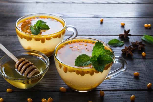 Vitamine gezonde duindoorn thee in glazen bekers met verse rauwe duindoorn bessen en kaneelstokjes, anijs sterren, munt en honing op een donkere keukentafel.