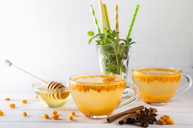 Vitamine gezonde duindoorn thee in glazen bekers met verse rauwe duindoorn bessen en kaneelstokjes, anijs sterren, munt en honing op een witte keukentafel.