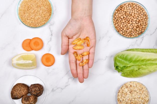 Vitamine voedingspillen bij de hand, natuurlijk geneeskundig supplement van biologisch vers fruit, volkoren granen en groente, gezond schoonheidsvoedsel dieet.