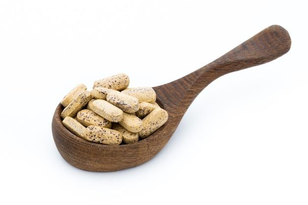 Vitaminecapsules in houten lepel