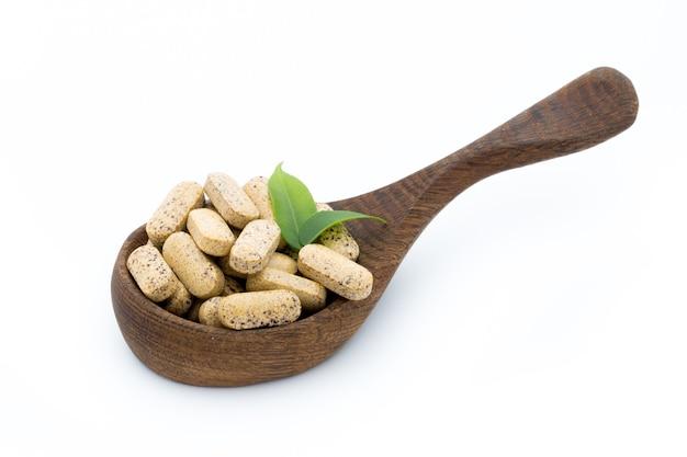 Vitaminecapsules op houten lepel met bladeren