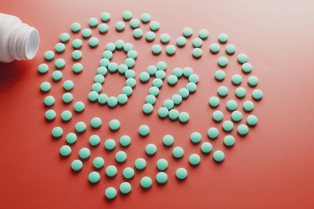 Vitaminen b 12 in de vorm van een hart op een rood substraat, gegoten uit een witte pot.