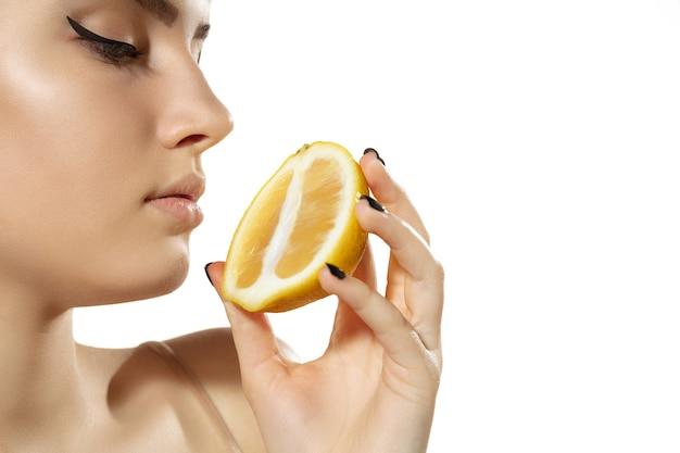 Vitaminen. close up van mooie jonge vrouw met sappige schijfjes citroen op white