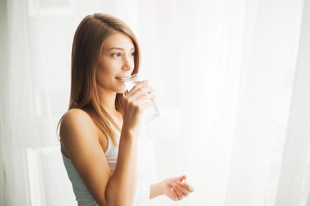 Vitaminen en supplementen. vrouw die een tablet neemt. sluit omhoog hand met een pil en de mond.