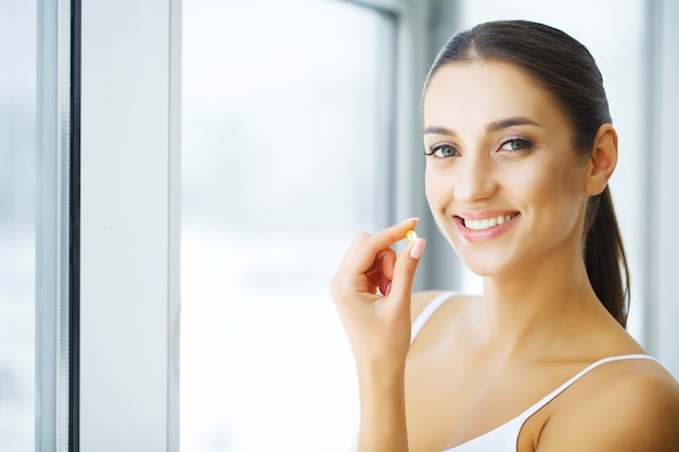 Vitaminen. gezond eten. gelukkig meisje met omega-3 visoliecapsule. gezonde voeding concept.