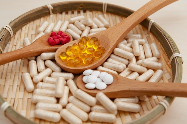Vitaminen, mineralen en voedingssupplementen in houten lepels in een gevlochten bamboe bord