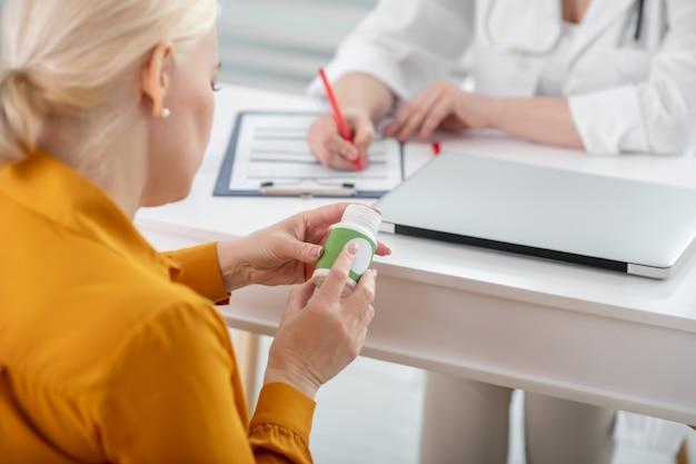 Vitaminen, supplementen. blonde volwassen vrouw in het geel kijken naar geneeskunde zitten tegenover de arts aan de tafel, geïnteresseerd.