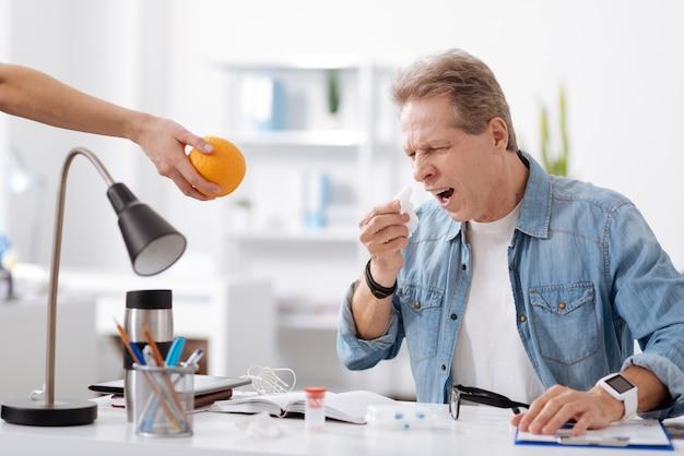 Vitamines innemen. gefrustreerde man die vrijetijdskleding draagt, zijn mond wijd openhoudt en naar sinaasappel kijkt