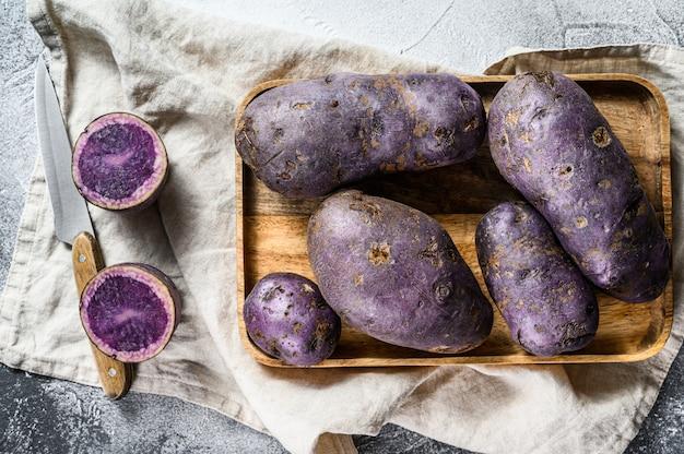 Vitelotte rauwe aardappel op een snijplank. . ruimte voor tekst