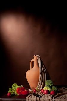 Vlaams stilleven op bruine achtergrond. clay vaas, broccoli, tomaten en rijp op tafel