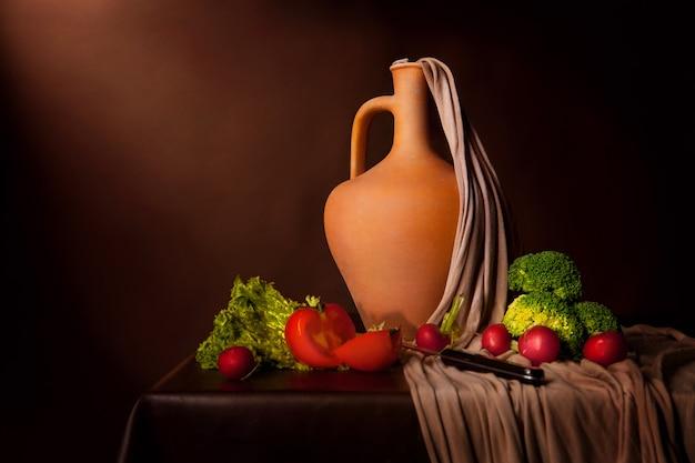 Vlaamse stijl levensstijl op bruine achtergrond. geschoten met studioverlichting. tomaten, broccoli, rijp, mes en een kan