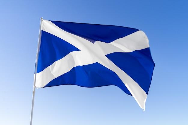 Vlag die van schotland tegen duidelijke blauwe hemel golven