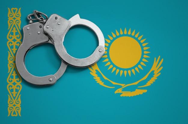 Vlag en politie handboeien van kazachstan. het concept van misdaad en delicten in het land