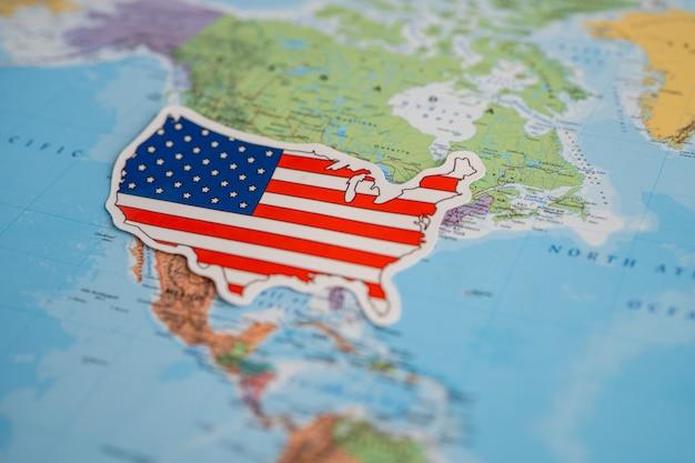 Vlag van amerika op de achtergrond van de wereldkaart vlag op de achtergrond van de wereldkaart