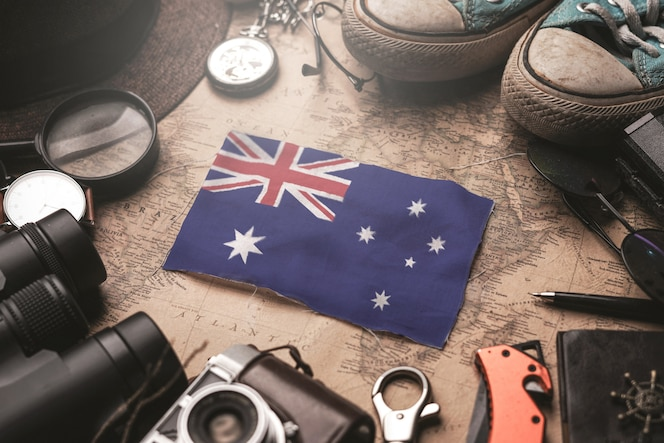 Vlag van Australië tussen de accessoires van de reiziger op oude vintage kaart. Toeristische bestemming Concept.