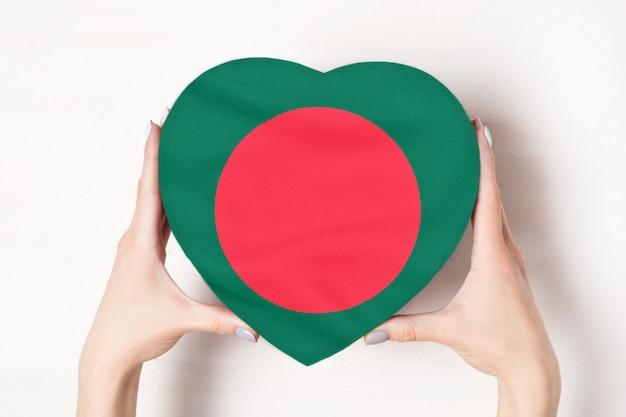 Vlag van bangladesh op een hartvormige doos in een vrouwelijke handen. wit