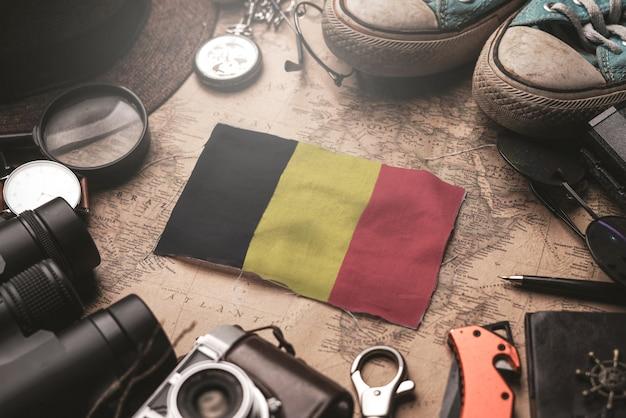 Vlag van belgië tussen accessoires van de reiziger op oude vintage kaart. toeristische bestemming concept.