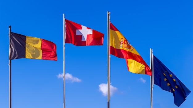 Vlag van belgië, vlag van zwitserland, vlaggen van spanje en vlag van de europese unie op blauwe hemel